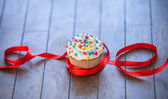 Cupcake and bow on wooden table. — Stock Photo
