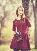 Redhead women  in a park with camera — Stock Photo