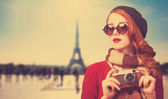 Redhead girl with camera on Paris background. — Stock Photo