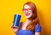 Redhead girl with drink and glasses on yellow background. — Stock Photo