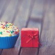 Cupcake and gift box on wooden table — Stock Photo #45420421