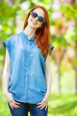 Redhead girl in the park in spring time. — Stock Photo