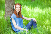 Redhead women with headphones in the park. — 图库照片