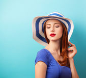 Redhead girl in hat on blue background. — Stock Photo