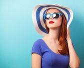 Garota ruiva com óculos escuros e chapéu em fundo azul. — Fotografia Stock