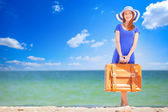 Redhead girl with suitcase on the beach in spring time. — Stock Photo