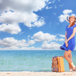Redhead girl with suitcase on the beach in spring time. — Stock fotografie #46010659