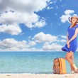Redhead girl with suitcase on the beach in spring time. — Stockfoto #46010659