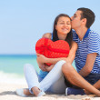 Young couple with gift on the beach in summer day. — Stock Photo
