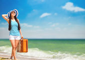 Young brunette girl with suitcase on the beach in summer time. — Stock Photo