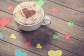 Cup with coffee and heart shape papers on wooden table. — Stock Photo