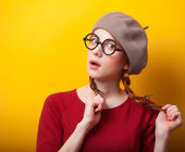 Redhead girl with pigtails on yellow background. — Photo