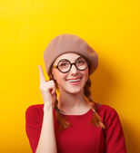 Redhead girl with pigtails on yellow background. — Stock fotografie