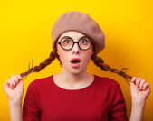 Redhead girl with pigtails on yellow background. — Foto Stock