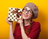 Redhead girl with pigtails and gift on yellow background. — Foto Stock