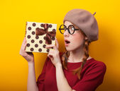 Redhead girl with suitcase on yellow background. — Stockfoto