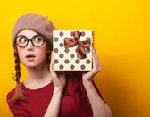 Redhead girl with suitcase on yellow background. — Stock Photo