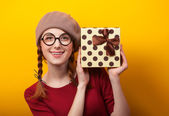 Redhead girl with pigtails and gift on yellow background. — Stok fotoğraf