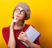 Redhead girl with notebook and pencil on yellow background. — Foto Stock