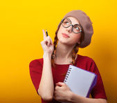 Redhead girl with notebook and pencil on yellow background. — 图库照片