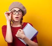 Redhead girl with notebook and pencil on yellow background. — Stok fotoğraf