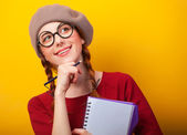 Redhead girl with notebook and pencil on yellow background. — Foto de Stock
