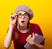 Redhead girl with notebook and pencil on yellow background. — Stock Photo