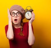 Redhead girl with alarm clock on yellow background. — Stok fotoğraf
