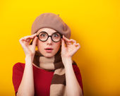 Redhead girl in glasses and scarf on yellow background. — Photo