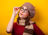 Redhead girl in glasses and scarf on yellow background. — Zdjęcie stockowe