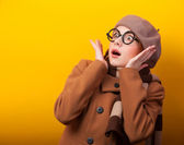 Redhead girl in coat and scarf on yellow background. — Foto de Stock