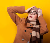 Redhead girl in coat and scarf on yellow background. — Stok fotoğraf