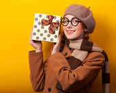 Redhead girl with gift box on yellow background. — Photo