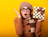 Redhead girl with gift box on yellow background. — Foto de Stock