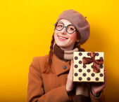 Redhead girl with gift box on yellow background. — Stock Photo