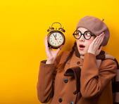 Redhead girl with alarm clock on yellow background. — ストック写真