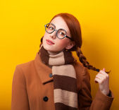 Redhead girl scarf and coat on yellow background. — Zdjęcie stockowe