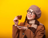 Redhead girl with coffee on yellow background — Foto de Stock