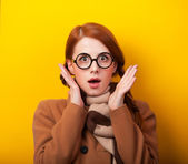 Redhead girl scarf and coat on yellow background. — Stok fotoğraf
