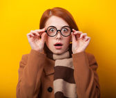 Redhead girl scarf and coat on yellow background. — 图库照片