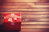 Red gift box on wooden table. — Stock Photo