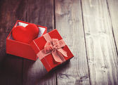 Red gift box with toy heart inside on wooden table.  — Stock fotografie