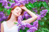 Redhead girl near lilac tree in the garden. — Stock Photo