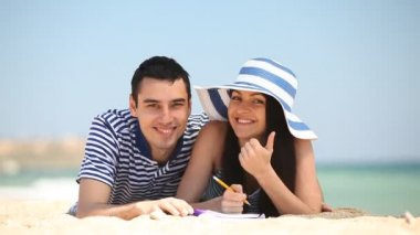 Young couple on the beach in summer day. — Stok video