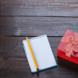 Notebook, gift and pencil on wooden table. — Stock Photo #46654571