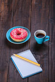 Cup of coffee with notebook and donut. — Stock Photo