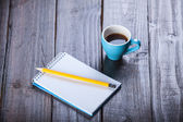 Cup of coffee witn notebook and pencil, on wooden table. — 图库照片