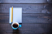 Cup of coffee with notebook and pencil, on wooden table. — 图库照片