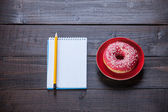 Notebook, donut and pencil on wooden table. — Stock Photo