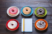 Notebook, donuts and pencil on wooden table. — Stock Photo